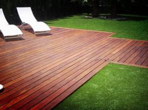 Suelo exterior en madera tropical en zona ajardinada junto piscina
